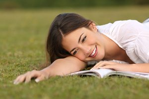 Beautiful woman lying on the grass reading a paper book.jpg