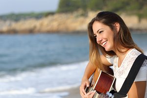 Beautiful guitarist woman playing guitar on the beach.jpg