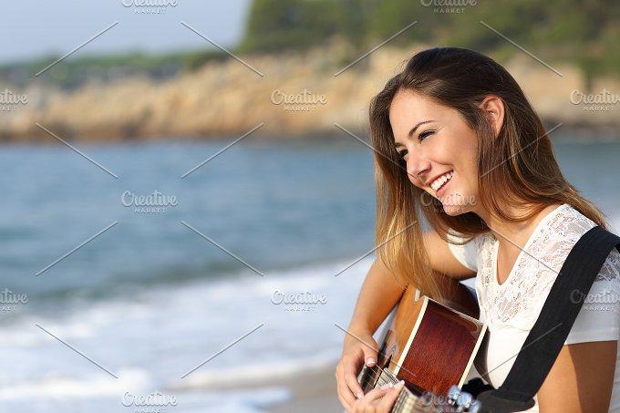 Beautiful guitarist woman playing guitar on the beach.jpg - Holidays