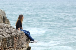 Casual woman sitting in a cliff watching the sea.jpg