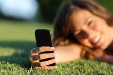 Close up of a happy teen girl hand using a smart phone on the grass.jpg