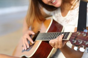 Close up of a woman playing guitar on the beach.jpg
