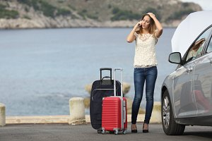 Worried traveler woman calling assistance beside a breakdown car.jpg