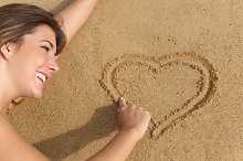 Happy woman in love drawing a heart on the sand of the beach.jpg