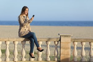 Woman texting in a smart phone on the beach.jpg