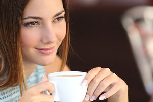 Pensive woman tasting coffee in a restaurant.jpg