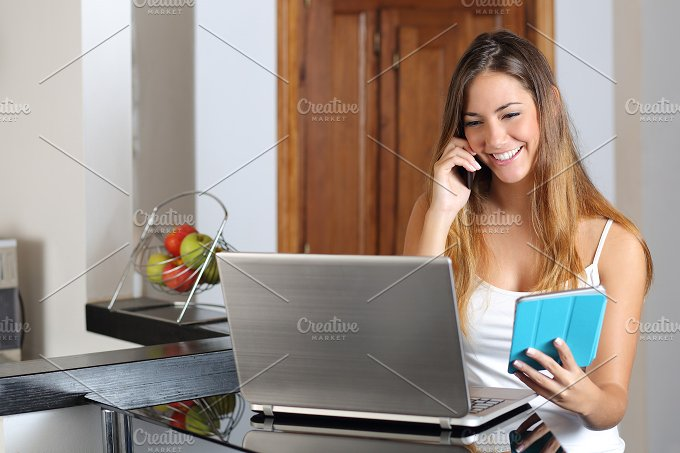 Woman multi tasking working with a laptop tablet and phone.jpg - Technology