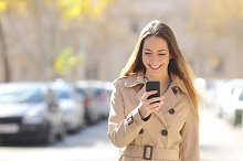Woman walking and using a smart phone on the street.jpg