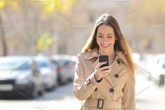 Woman walking and using a smart phone on the street.jpg - Technology