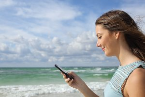 Side view of a girl using a smart phone on the beach.jpg