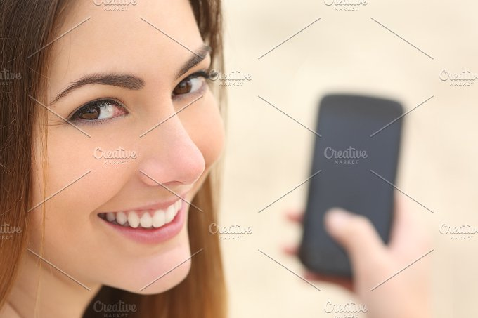 Portrait of a smiley woman using a smart phone.jpg - Technology