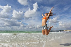 Happy girl jumping on the beach on vacations.jpg