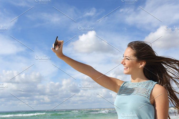 Teen photographing a selfie with a smart phone on the beach.jpg - Technology