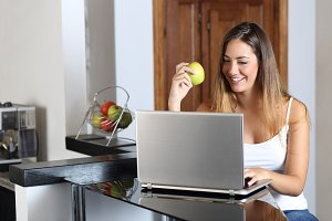 Entrepreneur woman browsing a laptop and eating at home.jpg