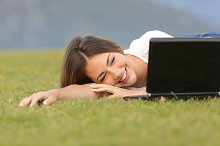 Happy woman watching videos in a laptop lying on the grass.jpg