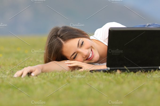 Happy woman watching videos in a laptop lying on the grass.jpg - Technology