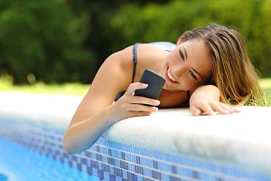 Woman using a smart phone in a poolside in summer.jpg
