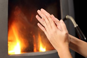 Woman hands heating in front a fire place.jpg