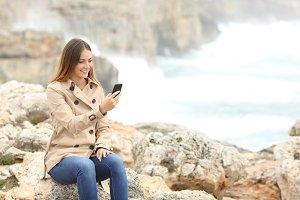 Woman using a smart phone in winter on the beach.jpg