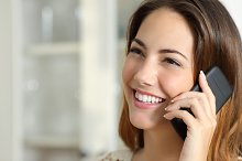 Woman talking on the mobile phone at home.jpg