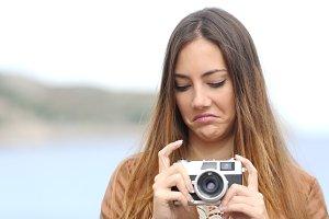 Upset woman looking her old photo camera.jpg