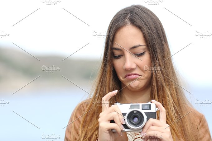 Upset woman looking her old photo camera.jpg - Technology
