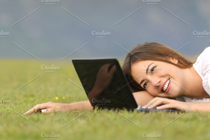 Happy woman browsing internet on a laptop on the grass.jpg - Technology