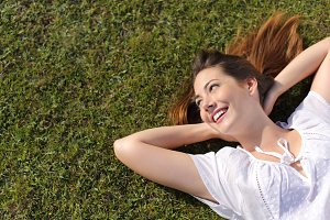 Relaxed happy woman resting on the grass looking at side.jpg