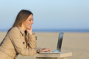 Self employed woman working with a laptop outdoors.jpg