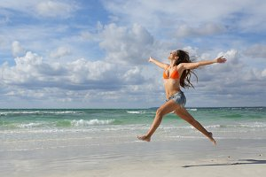 Happy woman jumping on the beach on holidays.jpg