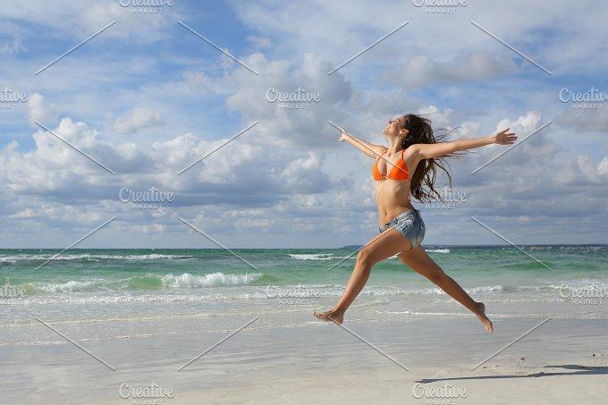 Happy woman jumping on the beach on holidays.jpg - Beauty & Fashion