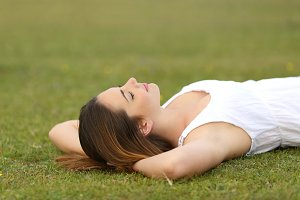 Relaxed woman lying on the grass sleeping in a tranquil scene.jpg