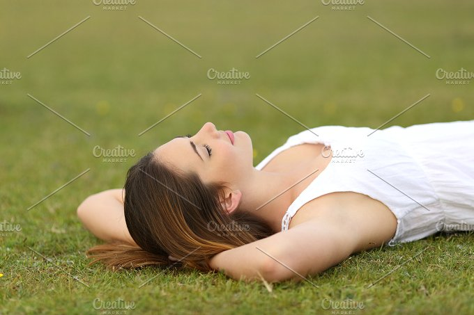 Relaxed woman lying on the grass sleeping in a tranquil scene.jpg - People