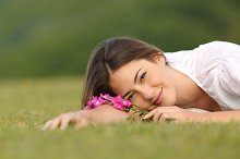 Relaxed woman resting on the green grass with flowers.jpg