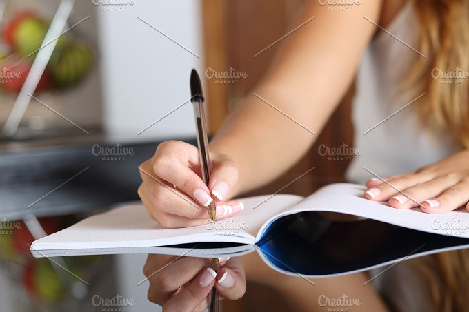 Woman writer hand writing in a notebook at home.jpg - Education