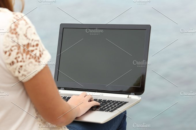 Woman working with a laptop and showing the screen.jpg - Technology