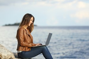 Self employed woman working with a laptop on the beach.jpg