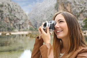 Tourist woman photographing a landscape in the mountain.jpg