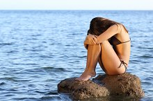 Worried woman sitting on a rock on the beach.jpg