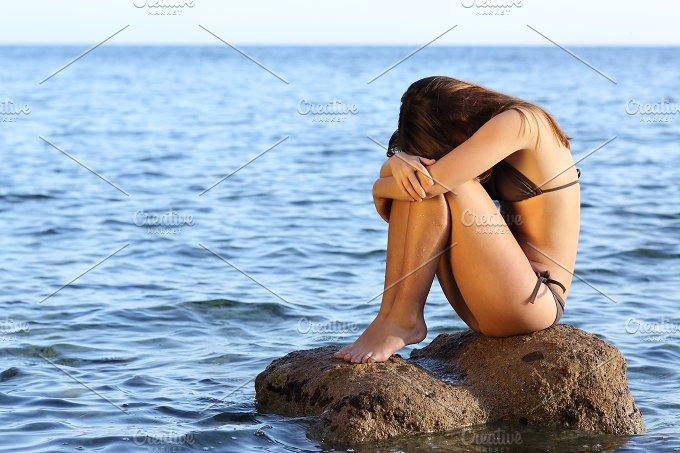 Worried woman sitting on a rock on the beach.jpg - People