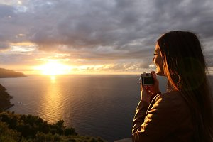 Traveler tourist girl taking photo in a sunset on vacations.jpg