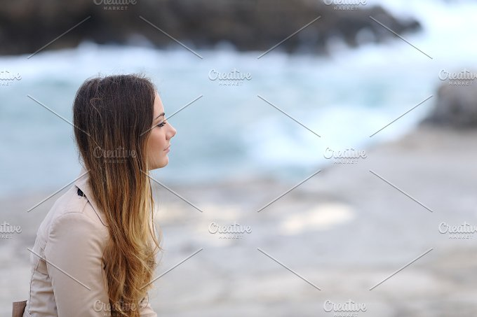 Profile of a pensive woman on the beach in winter.jpg - Beauty & Fashion
