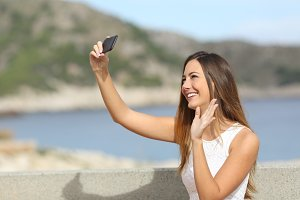 Woman waving while photographing a selfie with a smartphone.jpg