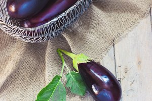 Organic Eggplants and Basket on the wooden background, still life