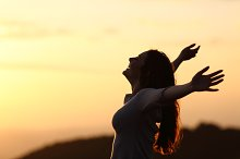 Back light of a woman breathing raising arms.jpg