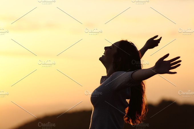 Back light of a woman breathing raising arms.jpg - Health