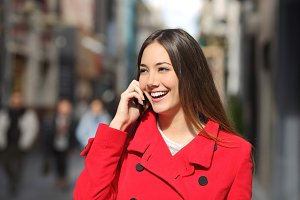 Cheerful woman talking on the phone in the street.jpg