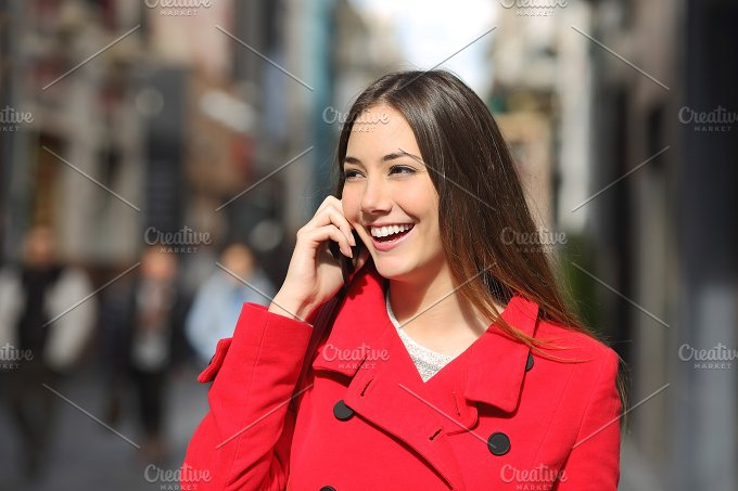 Cheerful woman talking on the phone in the street.jpg - Technology