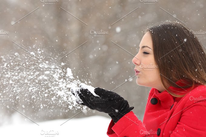 Candid woman in red blowing snow in winter.jpg - Holidays