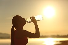 Fitness woman silhouette drinking water from a bottle.jpg